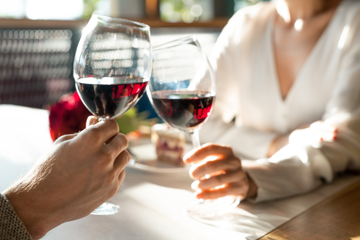 Hands of young man and his girlfriend clinking with wineglasses over table while enjoying romantic d...