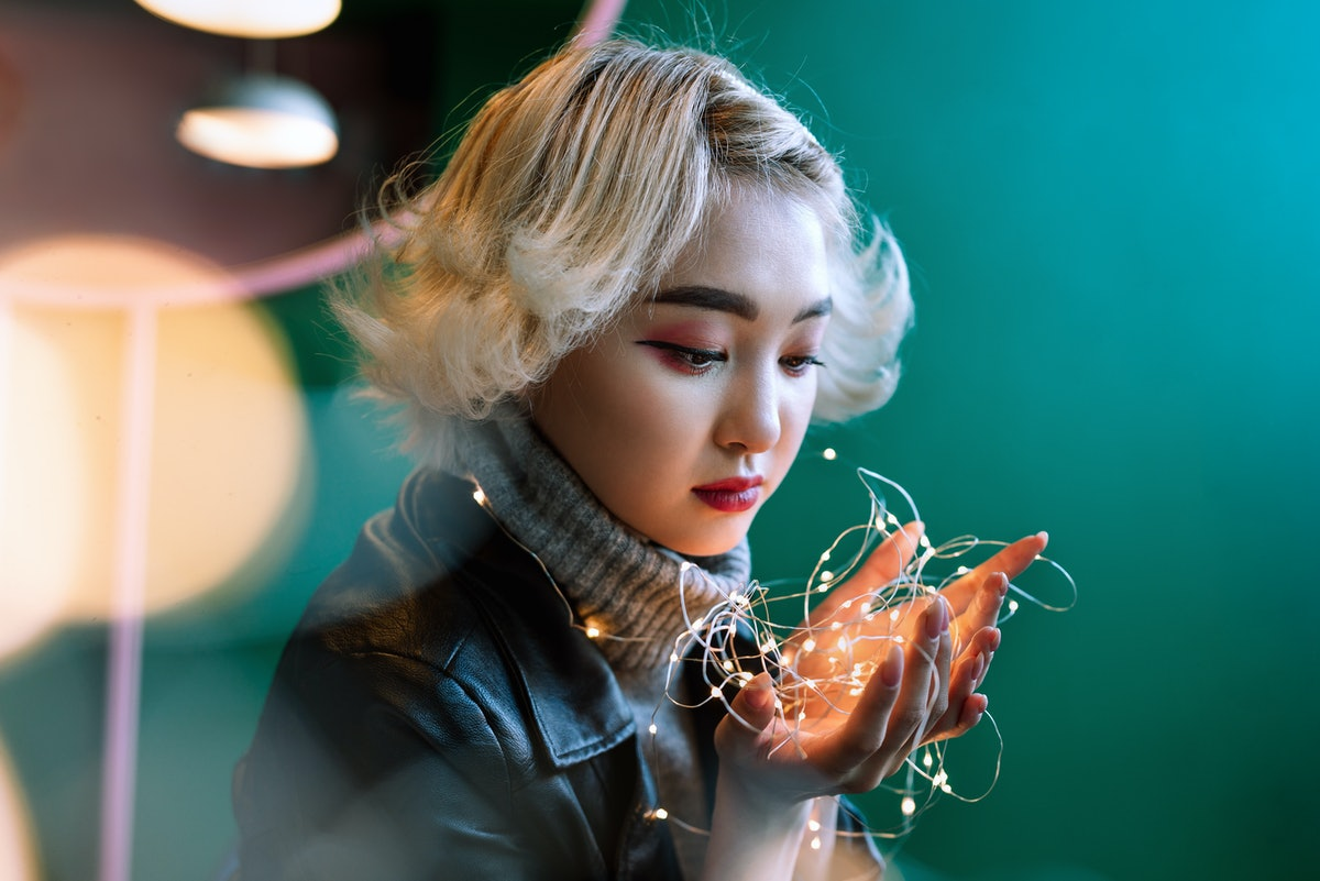 Young adult blonde female asian holding string of fairy lights with bokeh around, selective focus