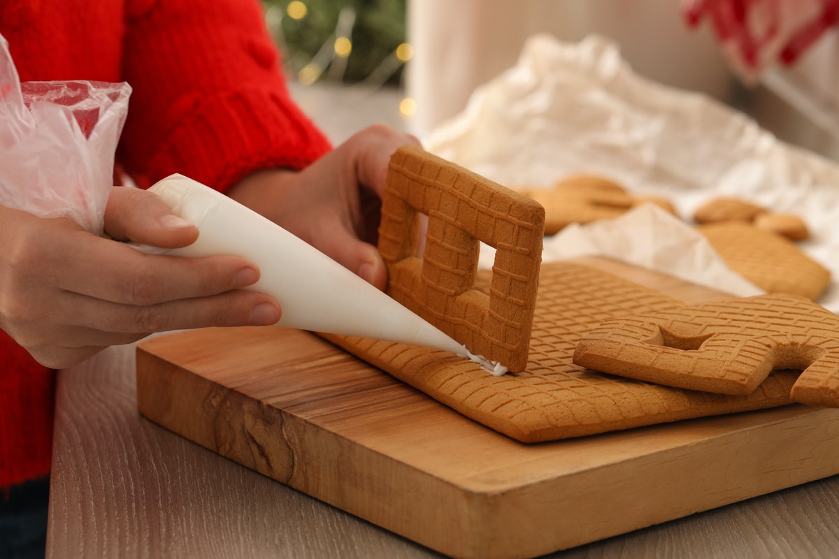 Woman making gingerbread house at wooden table, closeup