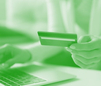 Close up image female sit at table using laptop hold credit card makes payment. E-commerce, e-bank modern tech usage, pay online, safety secure money spend distant purchase from home or office concept
