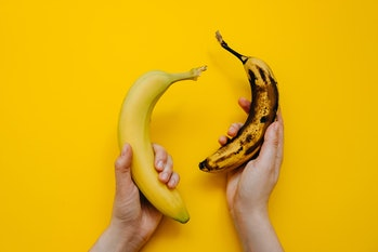 Human hands holding two bananas: fresh and ripe, on bright yellow background.