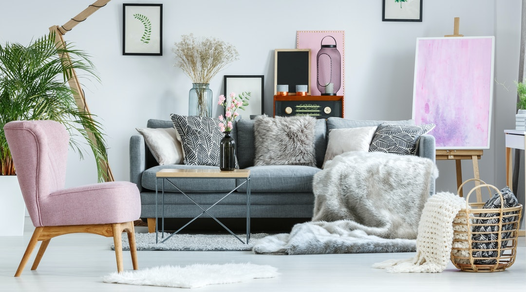 Cozy pastel room with vintage furniture, pink accents and armchair stylish interior