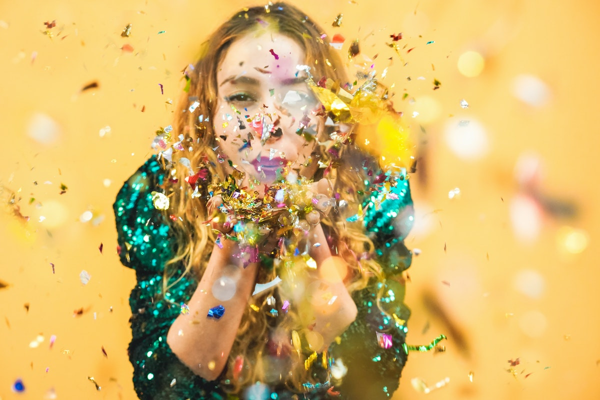 Happy fashion girl blowing confetti with yellow background - Young woman having fun at fest wearing trendy dress - Party, event and celebration concept - Focus on corianders holded in hands