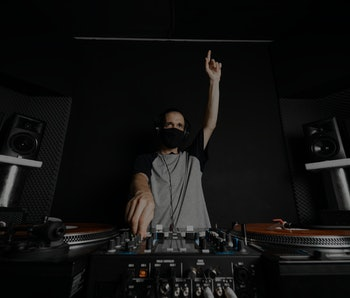 Professional DJ with reusable cloth face mask playing music raising his hand to cheer up the clients of the disco, with orange records and a gray T-shirt with dark blue sleeves