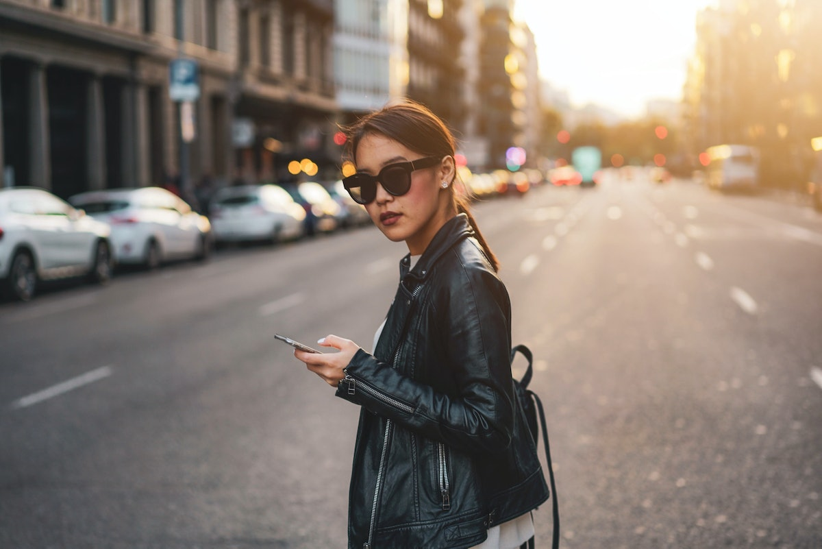 Successful business woman wearing black jeans, leather jacket and sunglasses is looking at the camera while crossing the road - Image