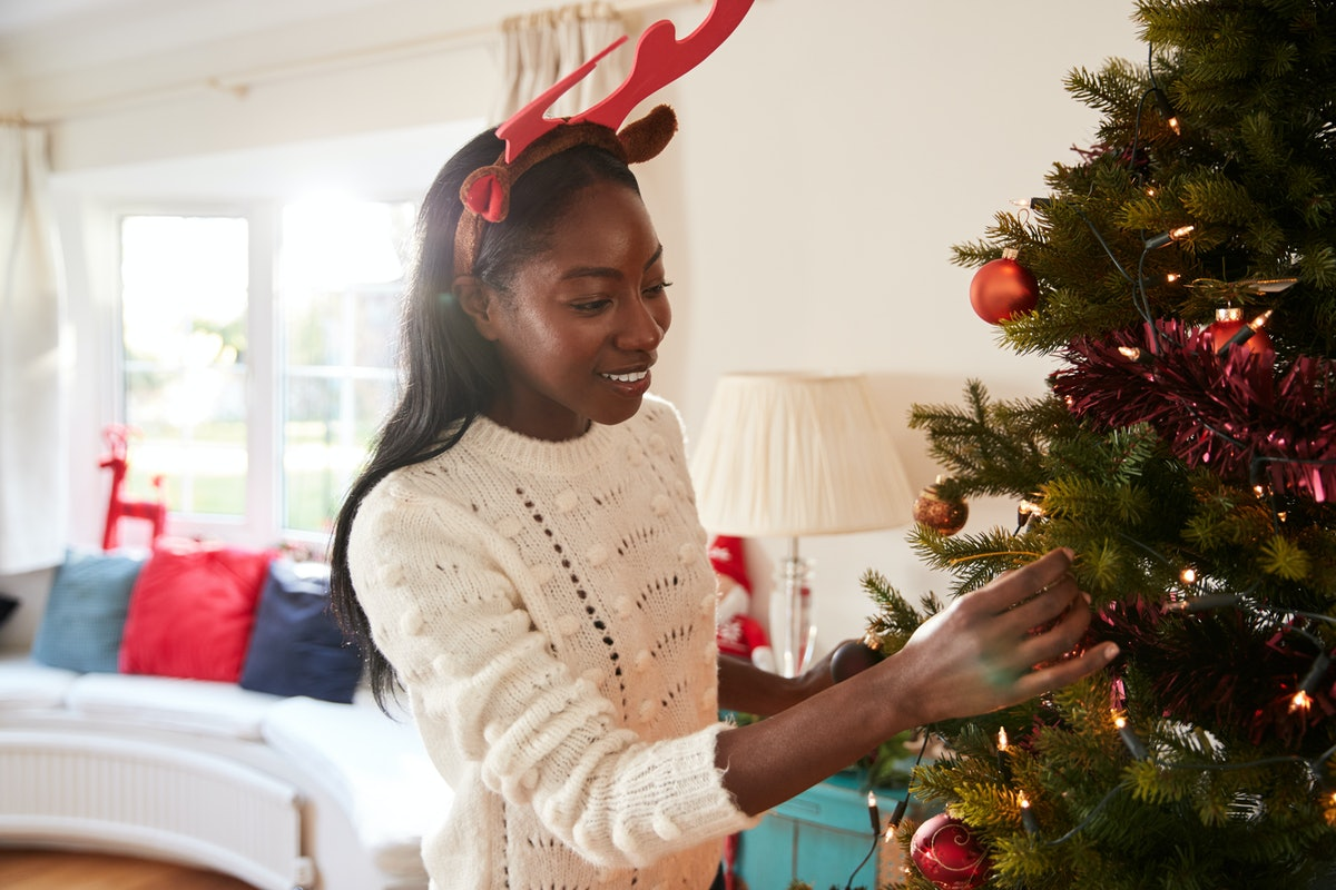 Woman Wearing Antlers Hanging Decorations On Christmas Tree At Home