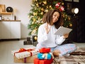 A young woman on the background of a Christmas tree with gifts, with a tablet has a video call or vi...
