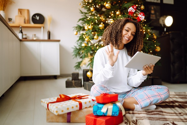 A young woman on the background of a Christmas tree with gifts, with a tablet has a video call or video chat with friends, family. Christmas online holiday. Stay home vacation.