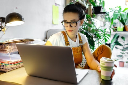 Young female gardener in glasses using laptop, communicates on internet with customer in home garden/greenhouse, hold reusable coffee/tea mug.Cozy office workplace, remote work, stay home concept