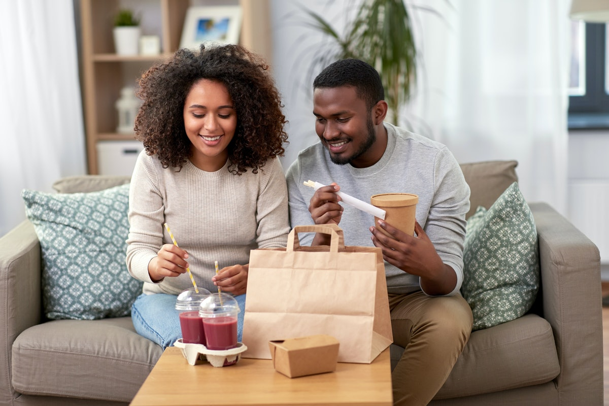 eating and people concept - happy african american couple with takeaway food and drinks at home