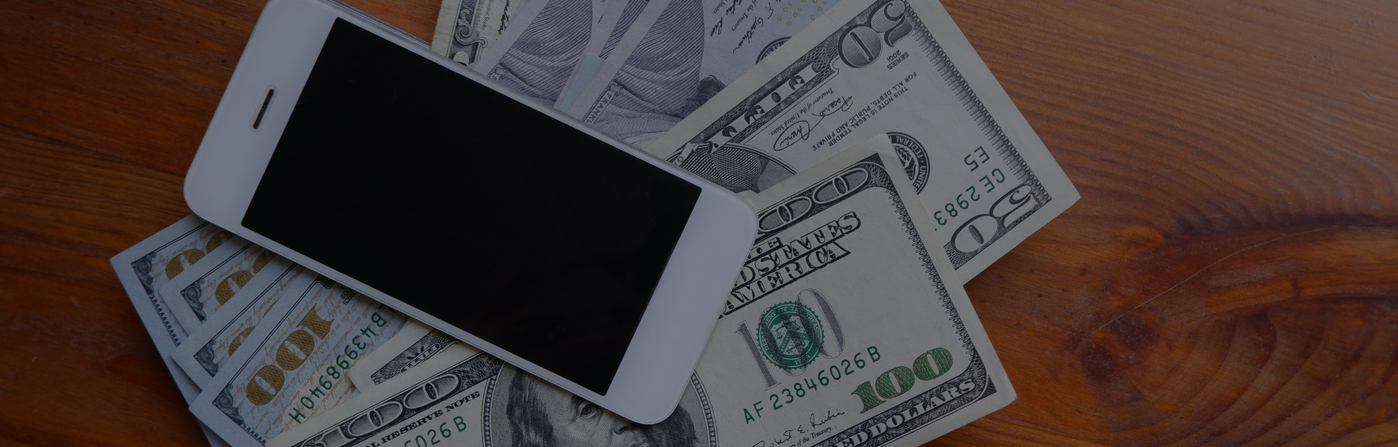 Mobile phone and money on a wooden background. The concept of making money using a smartphone. Pile of earned money using your phone.