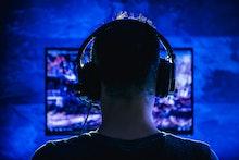 Men wearing headphones playing video games late at night