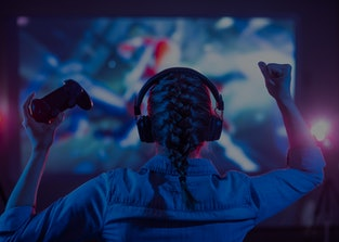 Girl in headphones plays a video game on the big TV screen. Gamer with a joystick. Online gaming wit...