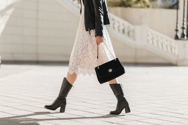 legs of attractive woman walking in street in high leather boots, fashionable outfit, holding purse,...