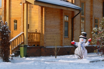 Snowman on the background of a wooden house.