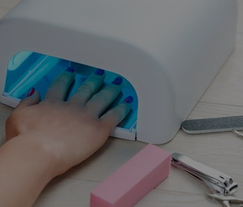 Manicured nails in UV lamp. Rays cure gel polish. Small nail art and manicure business.