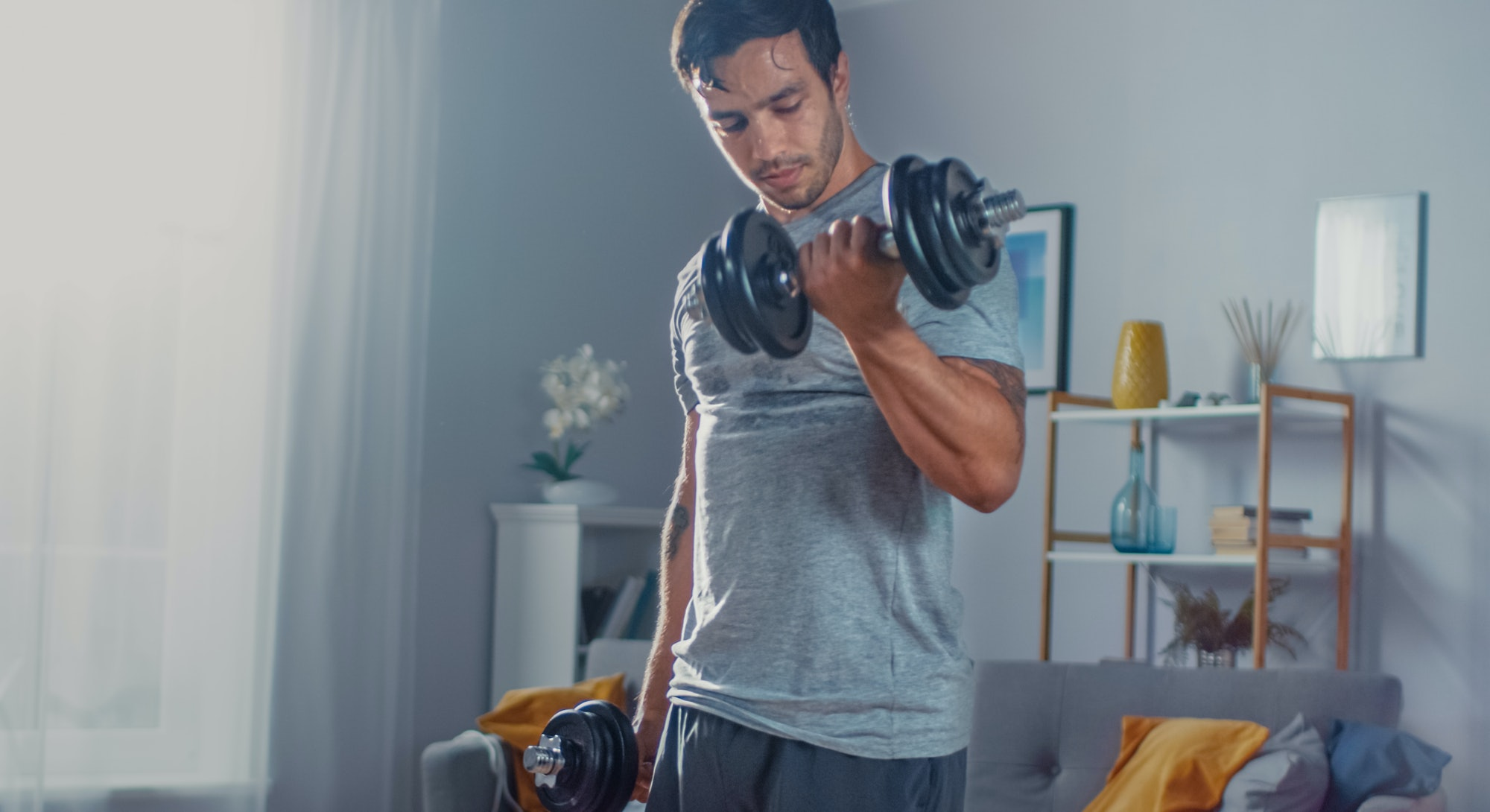 Strong Athletic Fit Man in T-shirt and Shorts is Doing Calf Raise Exercises with Dumbbells at Home in His Spacious and Bright Apartment with Minimalistic Interior.