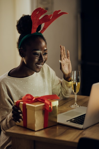 Happy African American woman waving while having video call over a computer at home on Christmas evening.