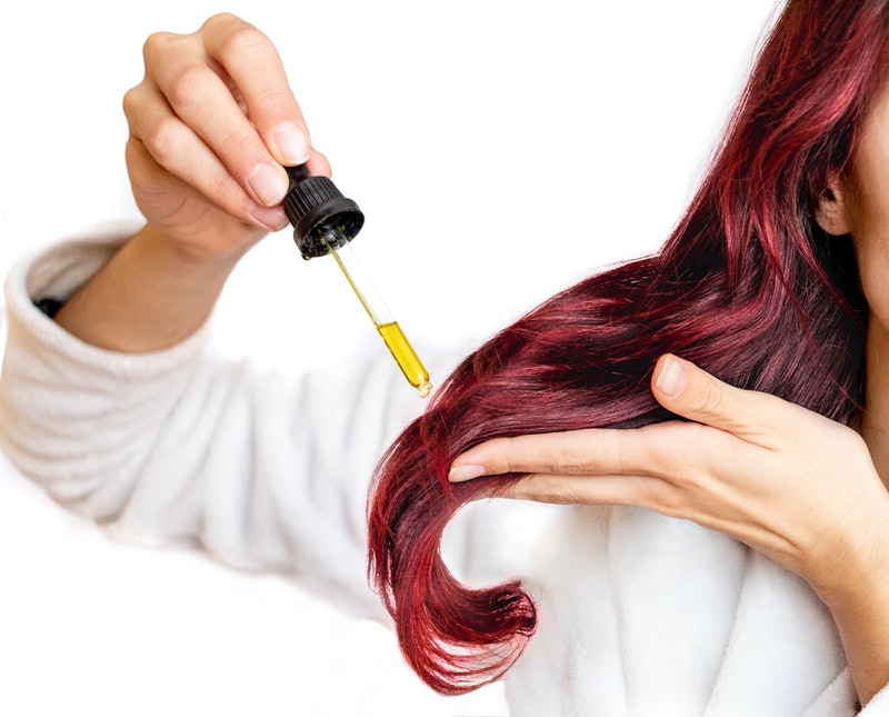Woman putting oil in her hair.