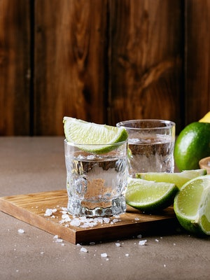 Tequila in a glass served with lemons, limes and salt over brown texture background