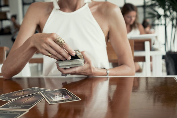 Woman is reading Tarot cards in cafe