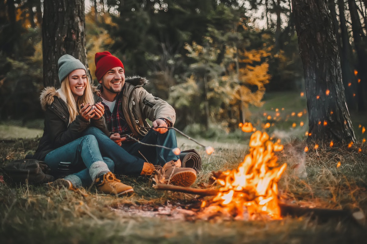 Traveler couple camping and roasting marshmallows over the fire in the forest after a hard day. Conc...