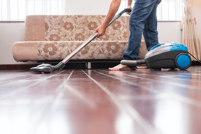 Cropped image of man vacuuming wooden floor