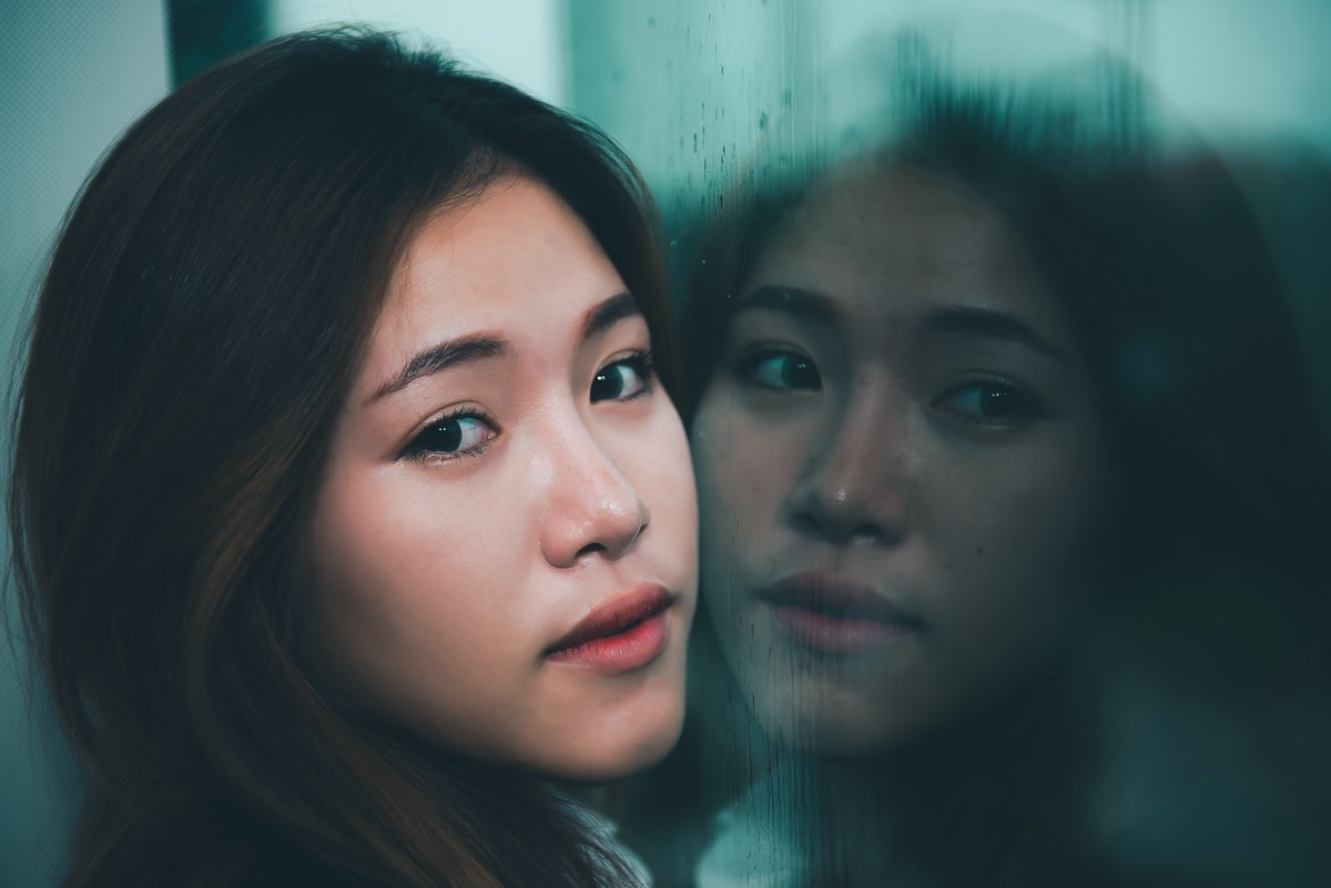 Closeup asian sad woman at mirror with reflection in a raining day vintage style,heartbreak woman co...