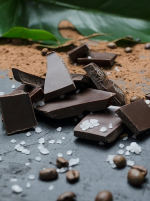 Delicious pile of pieces of chocolate, salt,cocoa powder, coffee beans on the black surface, green foliage on the background