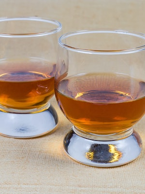 Two portions of brandy in brandy bowls on the tablecloth close-up