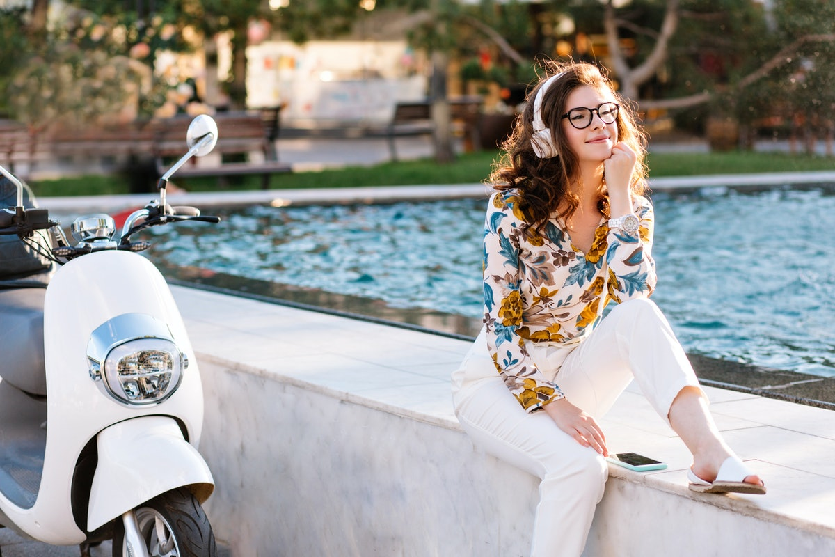 Dreamy girl with elegant hairstyle listening music and looking away, spending time near fountain. Am...