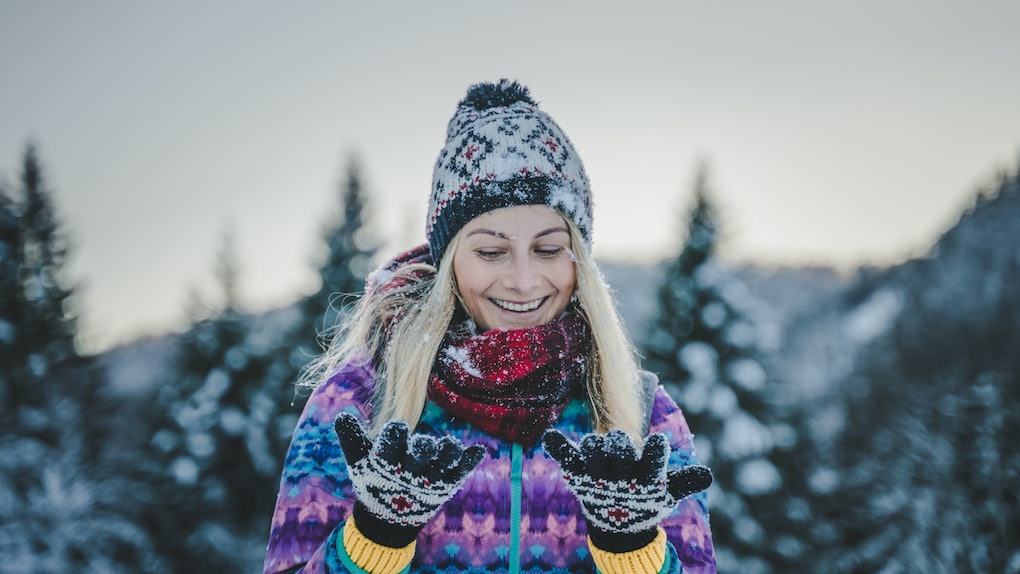 Young happy beautiful girl smiling and laughing in the snow, cozy and winter clothes, outdoor outfit, beanie and gloves