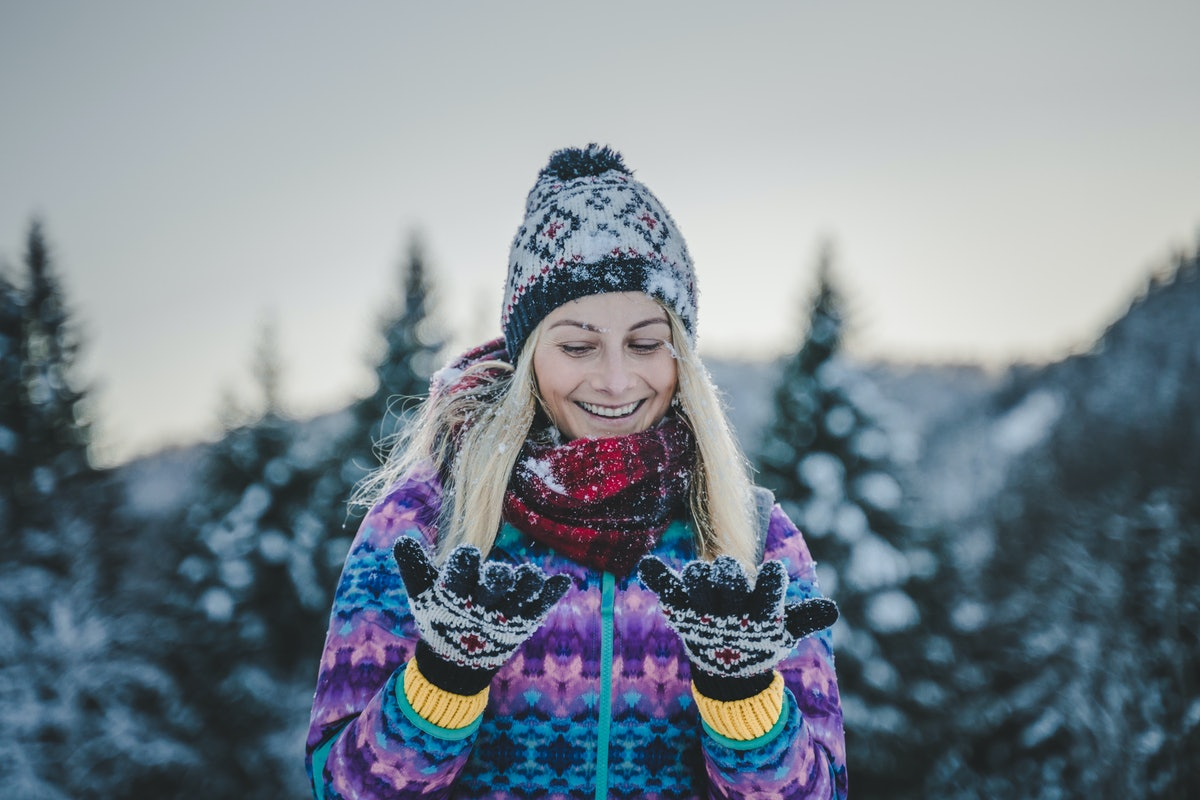 Young happy beautiful girl smiling and laughing in the snow, cozy and winter clothes, outdoor outfit...