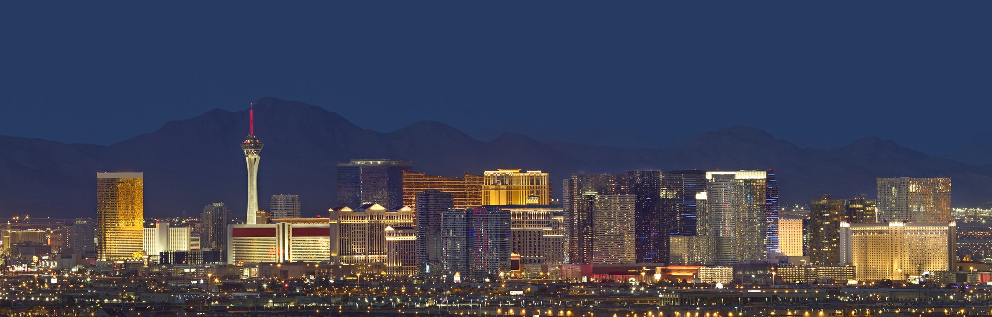 Horizontal photo of Las Vegas with mountain backdrop at night.