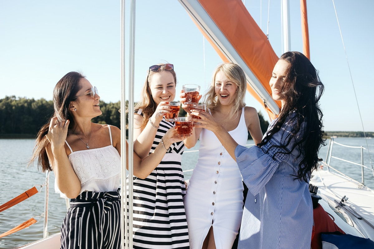 A group of friends on a cruise cheers their glasses and smile on a sunny summer afternoon.