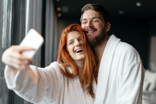 A couple poses for a selfie while wearing white robes and hanging out at a spa.