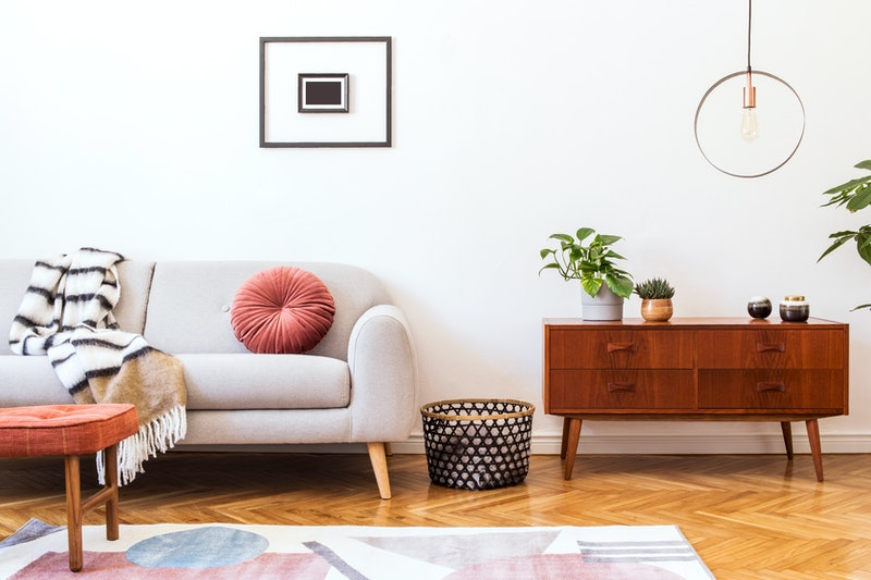 Stylish and retro interior of living room with design commode, gray sofa, round pendant lamp, vintage footrest, elegant accessories and mock up photo frames. Minimalistic home decor  with plants.
