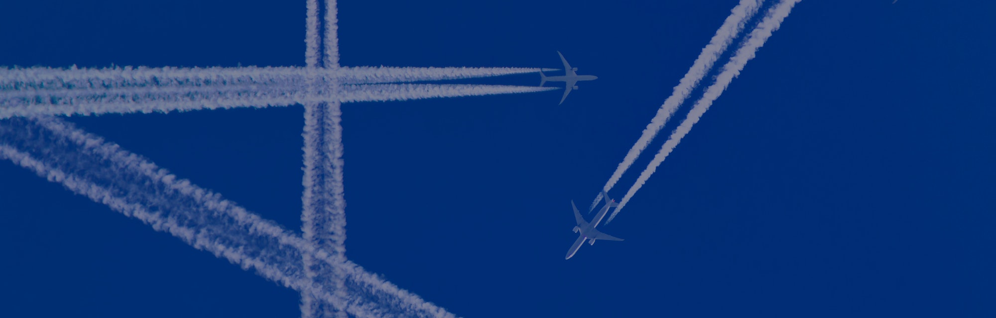 Several aircraft with white contrails