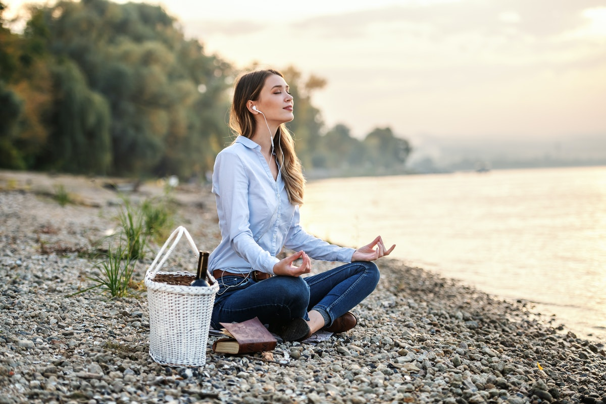 Attractive fashionable Caucasian young woman sitting on coast near river, listening music and medita...