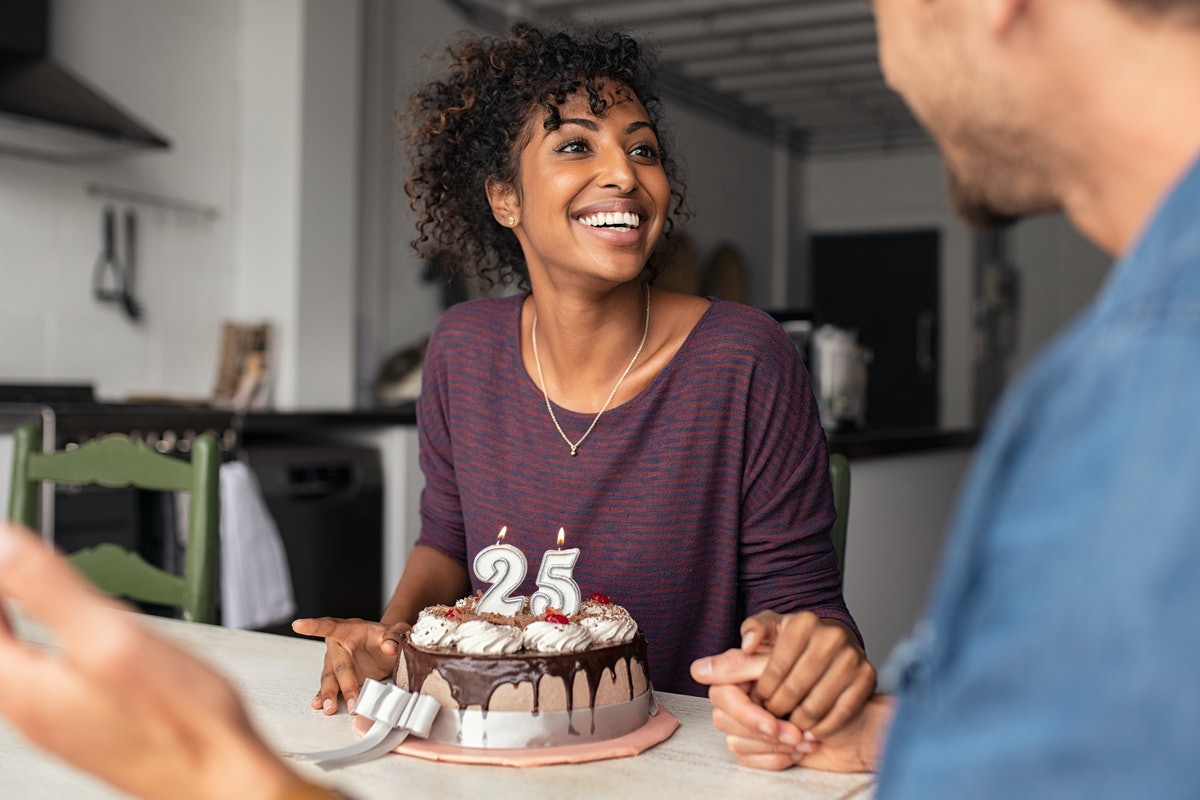 Multiethnic couple sitting at table and celebrating birthday at home. Young african girl surprised o...