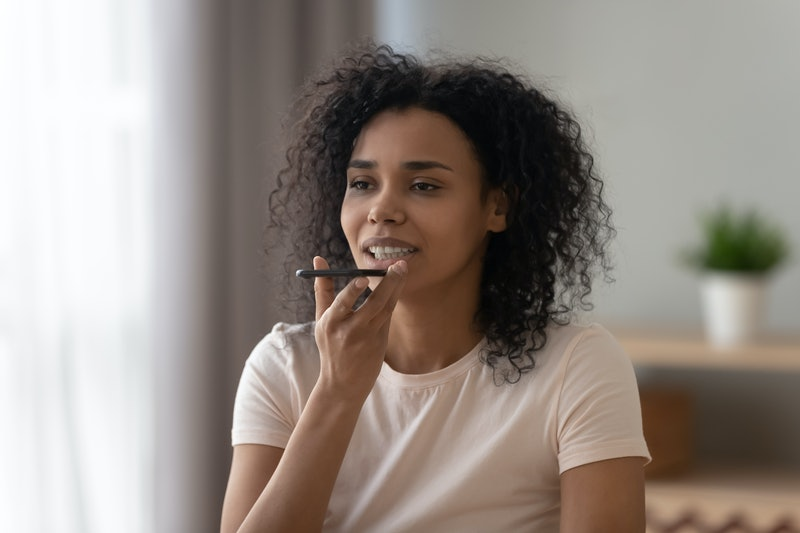 Beautiful african American young woman hold smartphone use digital assistant on device, black biracial millennial girl record voice message on cellphone, try new modern gadget app, technology concept