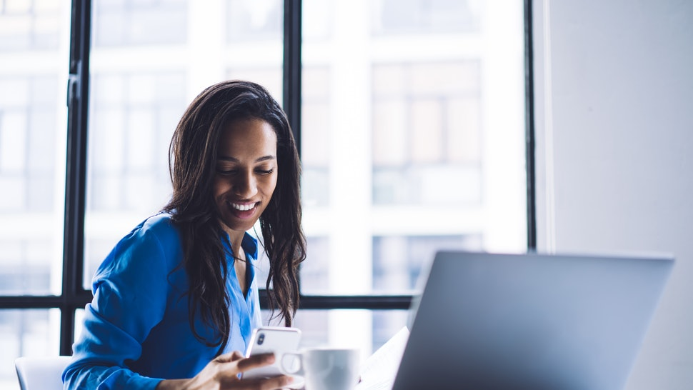 Young cheerful businesswoman in casual clothes chatting on smartphone joyfully while sitting in office at desk with laptop and coffee on glass window background