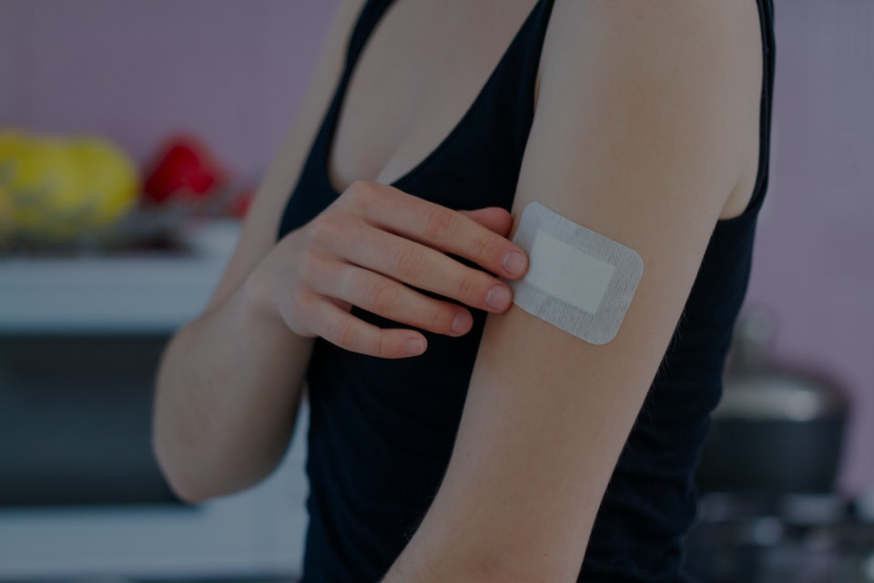Woman using a medical adhesive bandage on arm after vaccination, injection vaccine or medicine. First aid for cuts and wounds