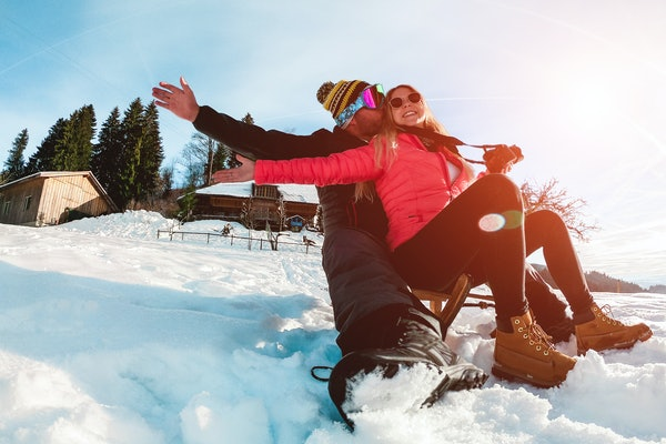 A happy couple slides down a snowy hill on a vintage sled while the sun shines on them.