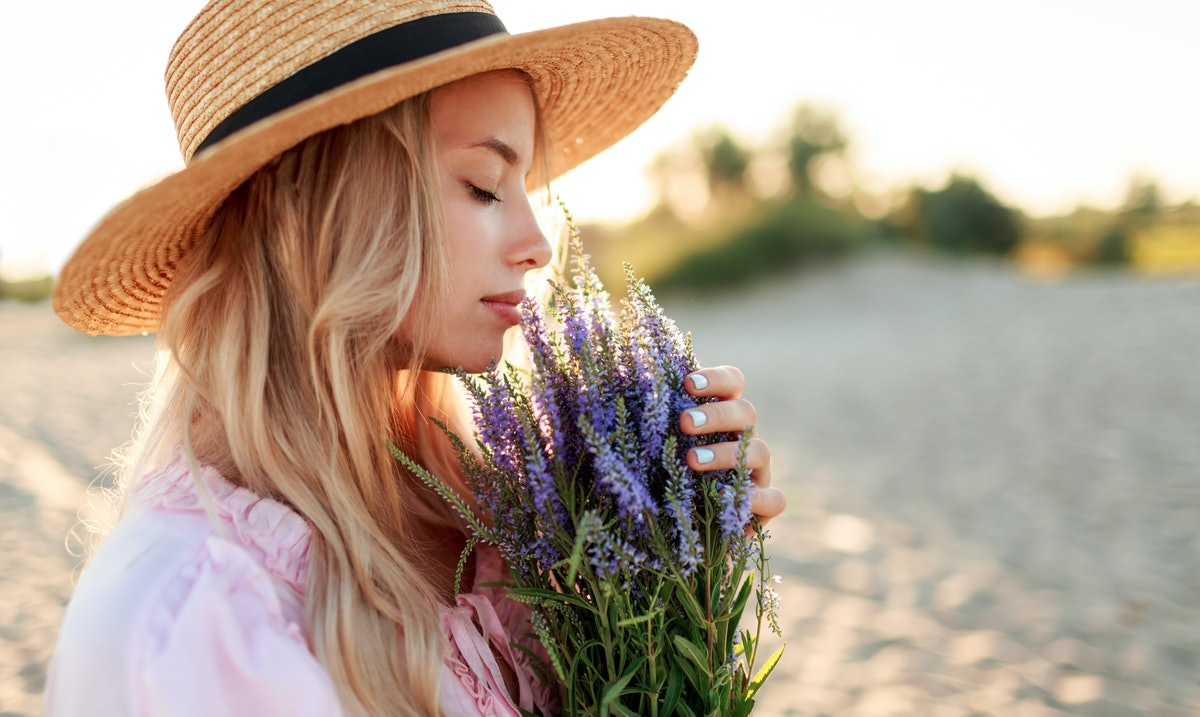 Romantic close up portrait  o charming blonde girl in straw hat  smells    flowers   on   the evening beach,  Warm sunset colors. Bouquet of lavender.