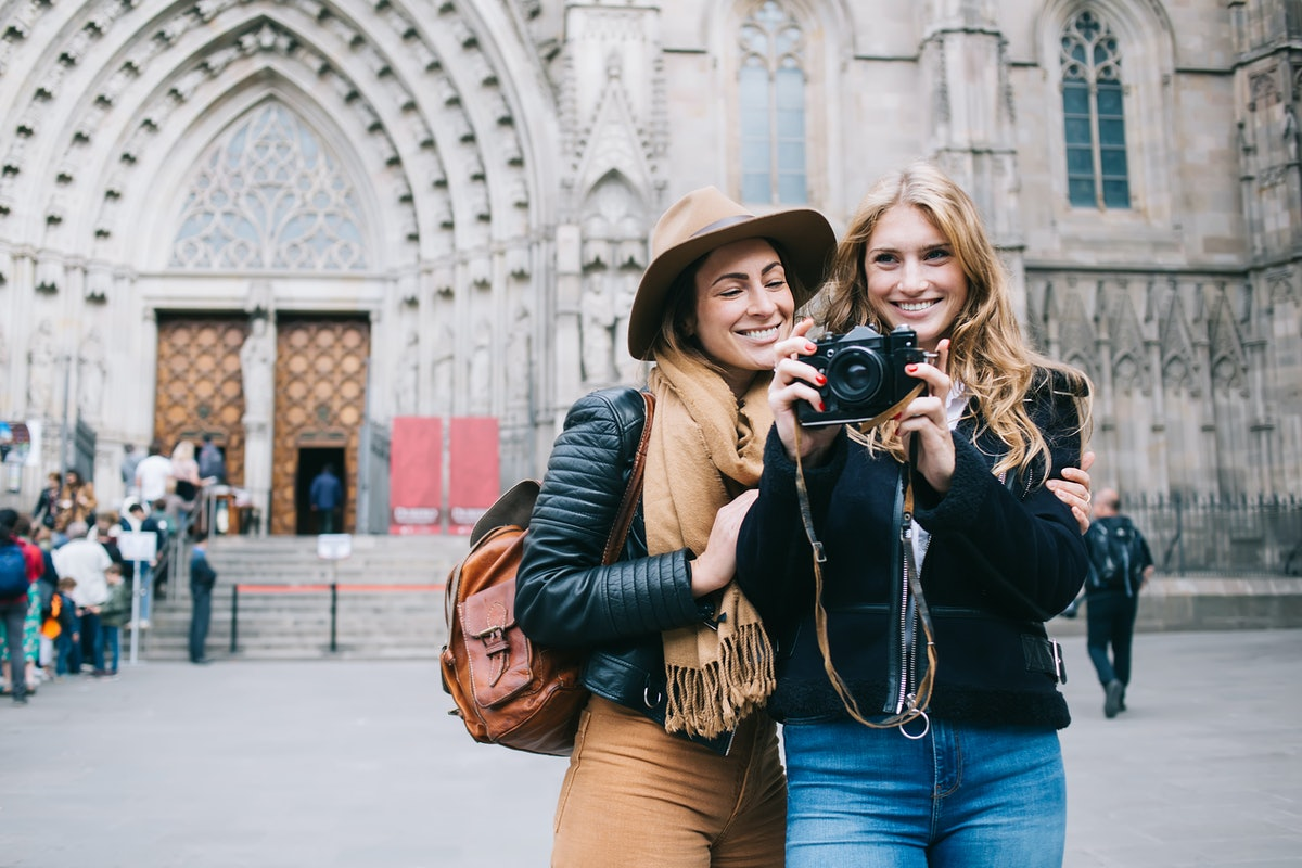 A happy couple stands nears a church in Barcelona, Spain and takes a picture while on spring break.
