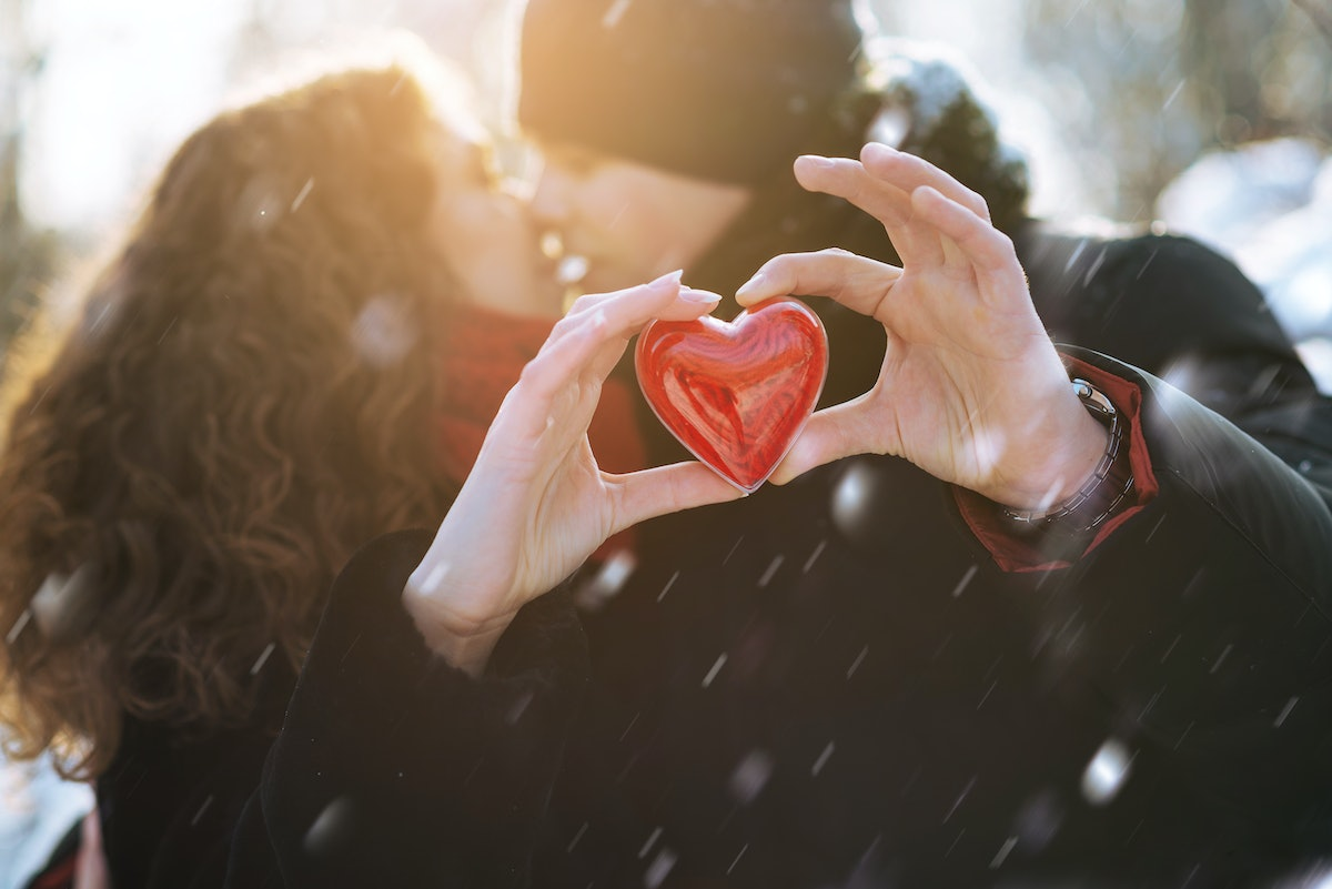 A couple kisses and holds out a plastic heart in front of them while it snows.