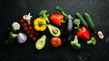 Ripe vegetables. Fresh vegetables on black stone background. Tropical fruits. Top view. Free space f...