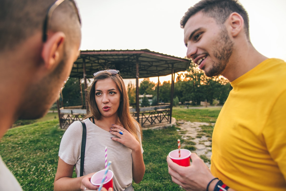 Three friends are enjoying beautiful sunset in the park, smiling and fooling around