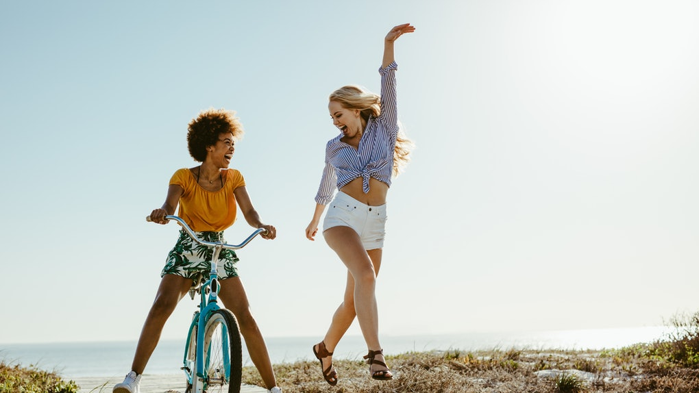 Two girls laugh while one rides a bike and the other dances down the boardwalk on a sunny day.